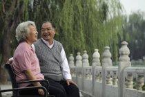 Coppia anziana seduta sul banco — Foto stock