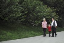 Vieux couple marchant avec petit-fils — Photo de stock