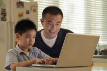 Padre e figlio che lavora al computer portatile — Foto stock
