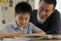 Hijo de padre ayudando con las tareas - foto de stock