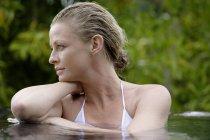 Женщина в бассейне в окружении деревьев — стоковое фото