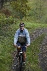 Senior man riding bike — Stock Photo