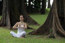 Mujer haciendo ejercicios de yoga bajo los árboles - foto de stock