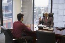 Бизнесмен, разговаривая с молодого человека — стоковое фото