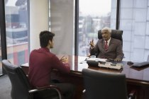Businessman talking with younger man — Stock Photo