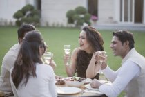 Friends drinking wine at table — Stock Photo