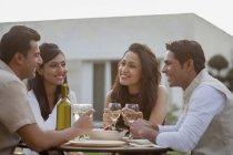 Freunde, trinken Wein am Tisch — Stockfoto