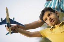 Niño jugando con avión de juguete - foto de stock