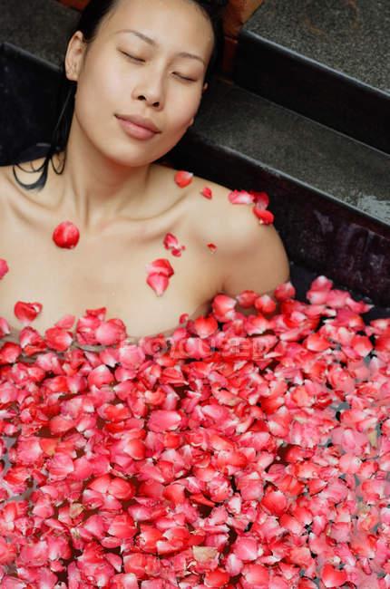 Женщина в ванне с лепестками роз — стоковое фото