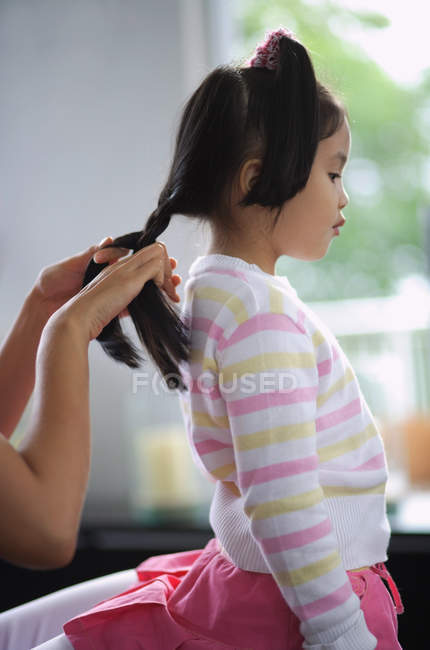 Girl braided by mother — Stock Photo