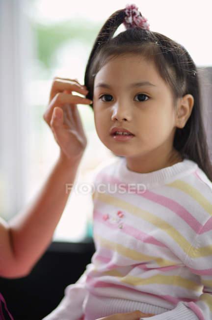 Ragazza che osserva via mentre la madre ripiegando i suoi capelli — Foto stock