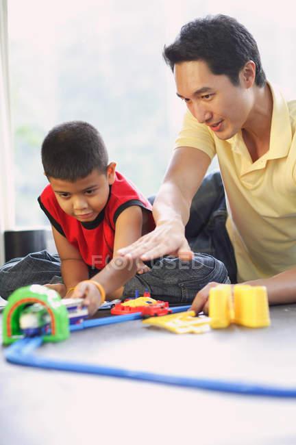 Padre e figlio che giocano con insieme del treno — Foto stock