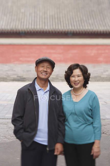 Homem e uma mulher de pé na rua e sorrindo — Fotografia de Stock