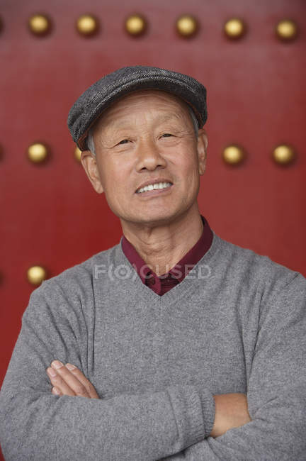 Old man crosses his arms — Stock Photo