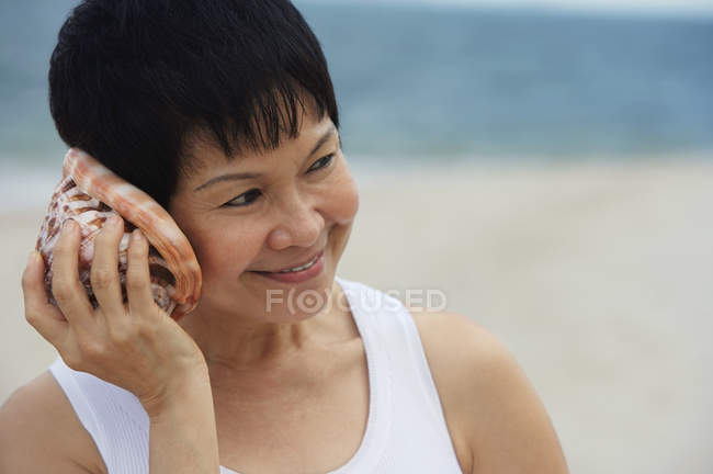 Woman listening sea shell — Stock Photo