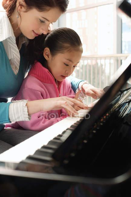 Fille apprendre à jouer du piano avec tuteur — Photo de stock