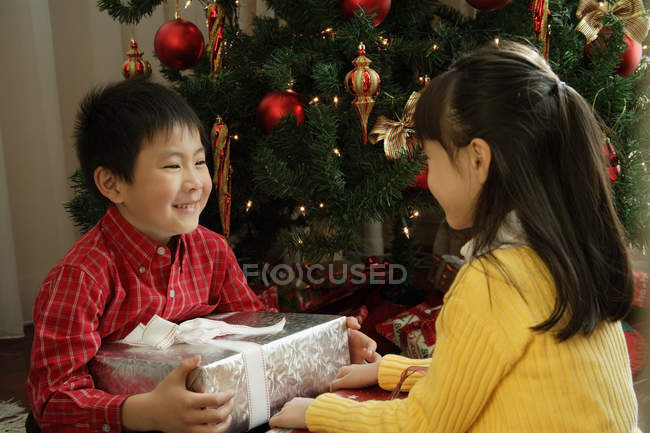 Boy and girl sitting with presents — Stock Photo