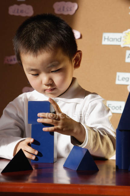 Schoolboy playing with building blocks — Stock Photo