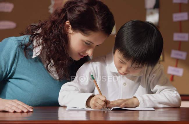 Вчитель допомагає молодий студент — стокове фото
