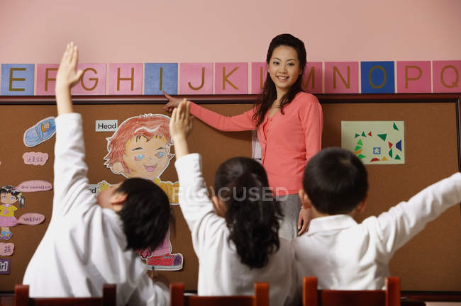 Teacher teaching alphabet with students — Stock Photo