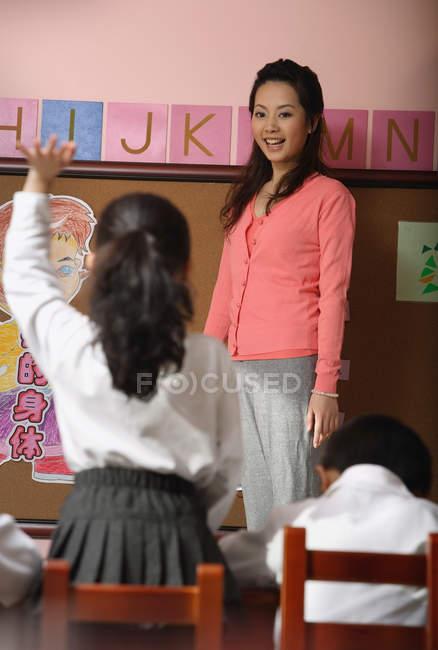 Chica levantando la mano y responder a profesor — Stock Photo