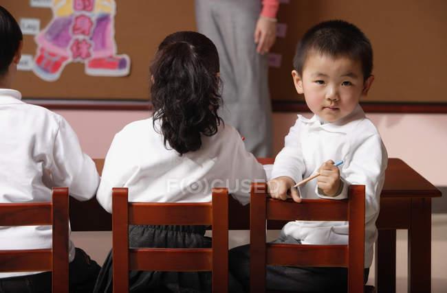 Étudiants assis en classe avec l'enseignant — Photo de stock