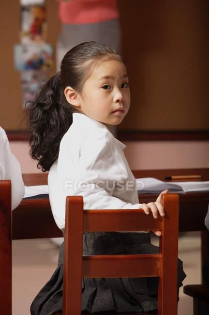 Écolière en classe en tournant la tête — Photo de stock