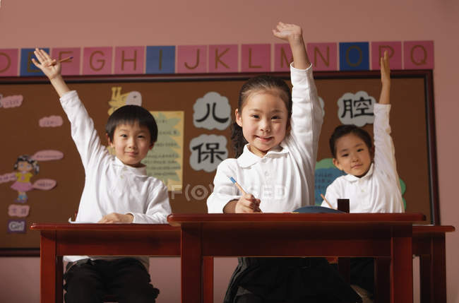 Students in class raising hands — Stock Photo
