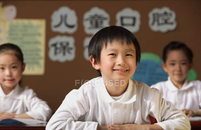 Estudiantes sentados en mesas en clase - foto de stock