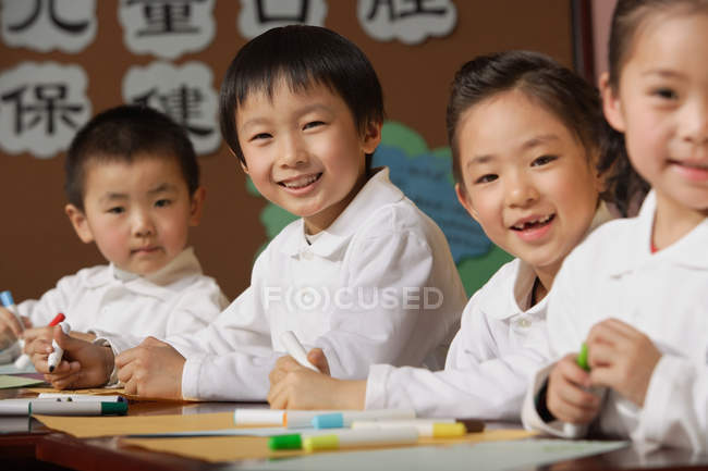 Studenti seduti sui tavoli in classe — Foto stock