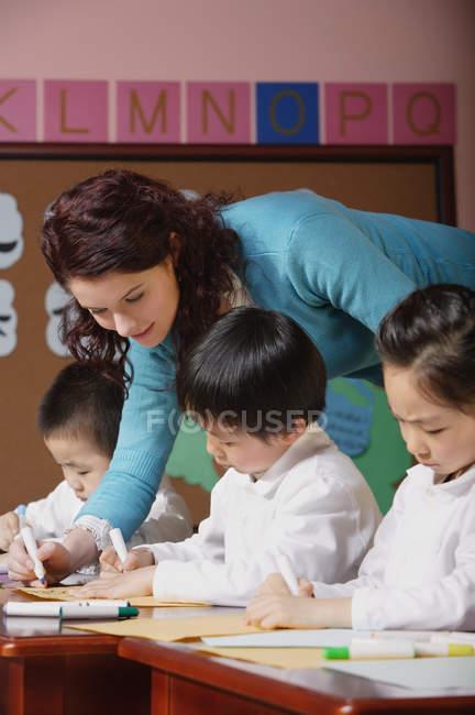 Insegnante che esamina opere dei bambini — Foto stock