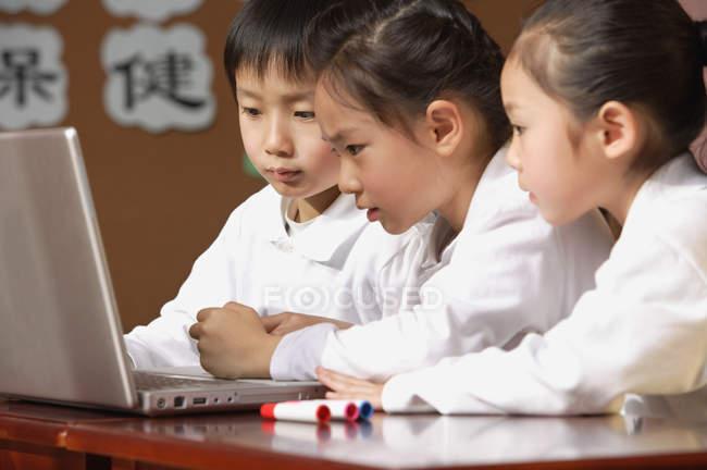 Schüler nutzen gemeinsam Laptop — Stockfoto