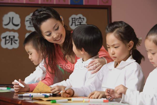 Школярі з вчителем в класі — стокове фото