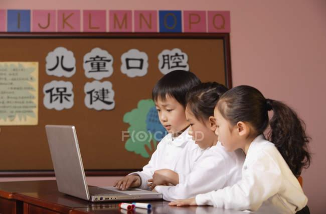 Schüler nutzen gemeinsam Laptop im Unterricht — Stockfoto