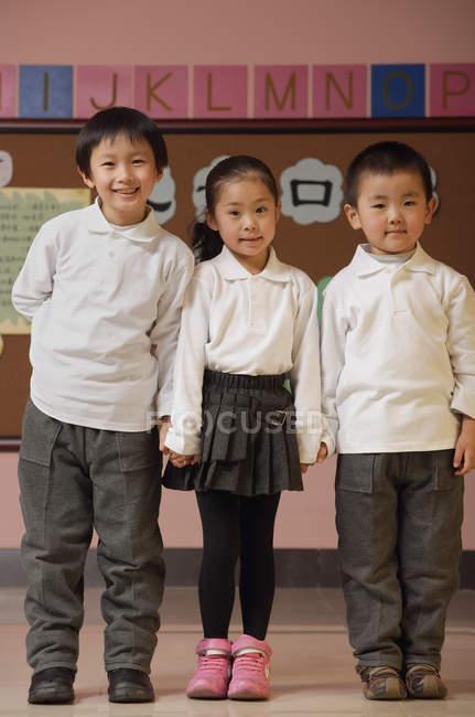 Студенты, стоящие против булавки в классе — стоковое фото