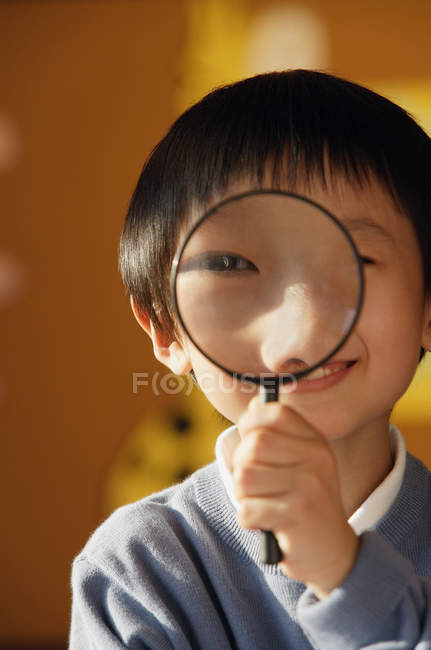 Schoolboy looking at camera with magnifying glass — Stock Photo