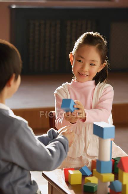 Хлопчик і дівчинка, граючи з будівельних блоків — стокове фото