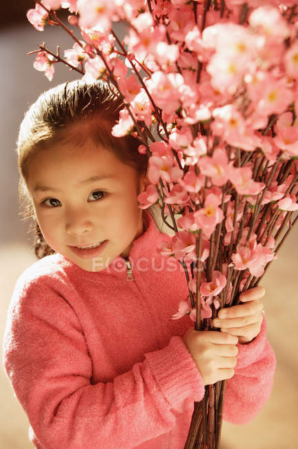 Asian girl with cherry blossom branches — Stock Photo