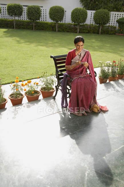 Woman in sari knitting — Stock Photo