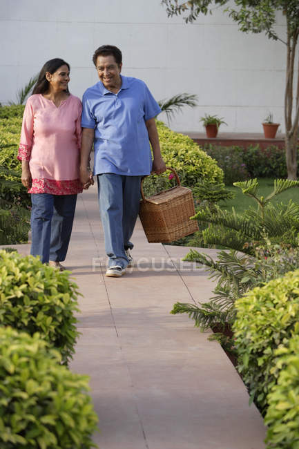 Couple walking with picnic basket — Stock Photo