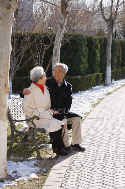 Elderly couple sitting on park bench — Stock Photo