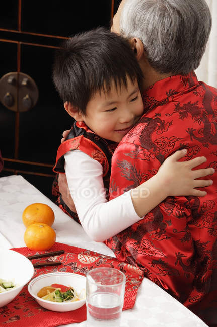 Boy hugging grandfather — Stock Photo