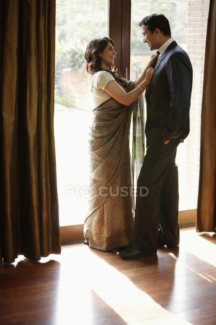 Couple standing near window — Stock Photo