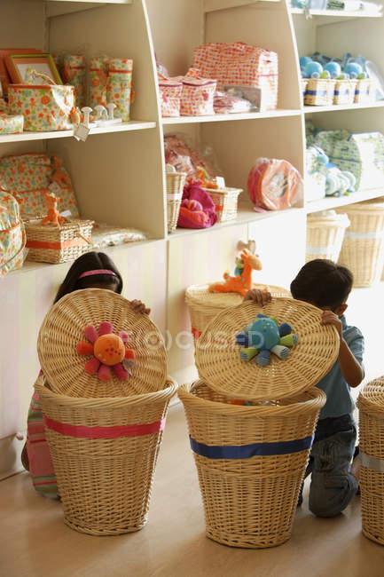 Bambini in negozio, dietro i cestini — Foto stock