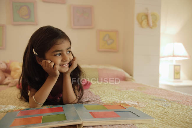 Girl reading book on bed — Stock Photo