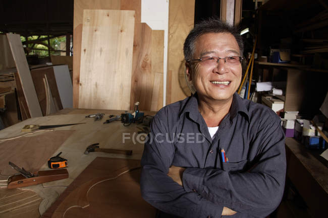Craftsman standing in front of work bench — Stock Photo