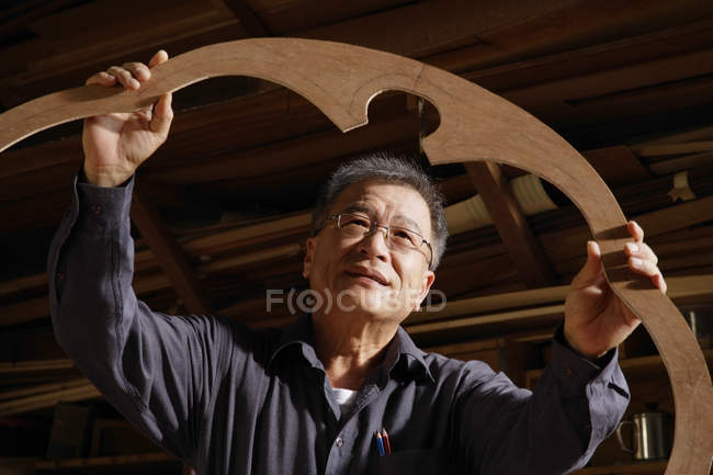 Craftsman looking at creation in artisan shop — Stock Photo