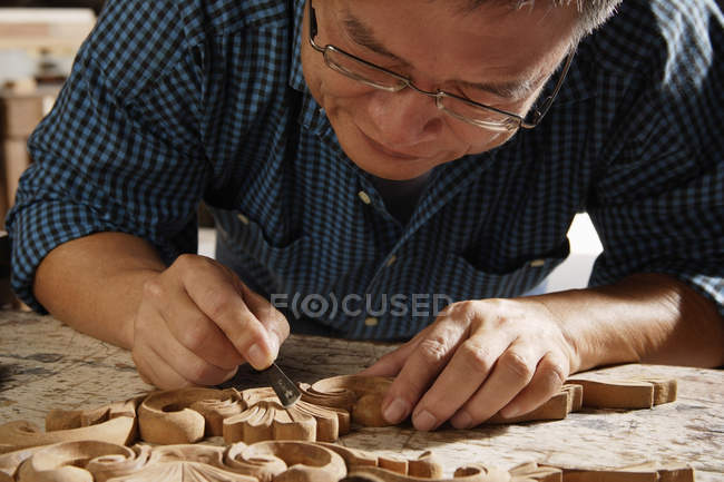 Craftsman carving wood — Stock Photo