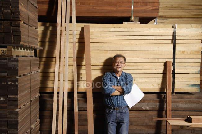 Homme appuyé contre une pile de bois — Photo de stock