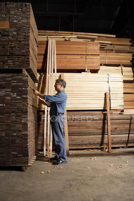 Homme travaillant dans la cour à bois — Photo de stock